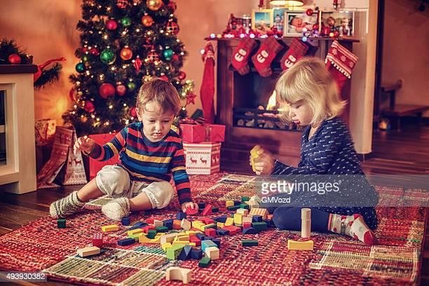 Adorable Kinder spielen in vor Weihnachtsbaum