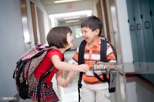 Adorables enfants avec sacs à dos riant dans le couloir de l'école élémentaire