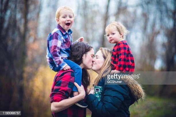 entzückende kinder mit ihren eltern - lgbtq familie mit kindern - herbst winter kollektion stock-fotos und bilder