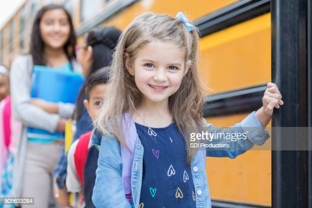adorable kindergarten age girl boards school bus - public service announcement stock photos and pictures