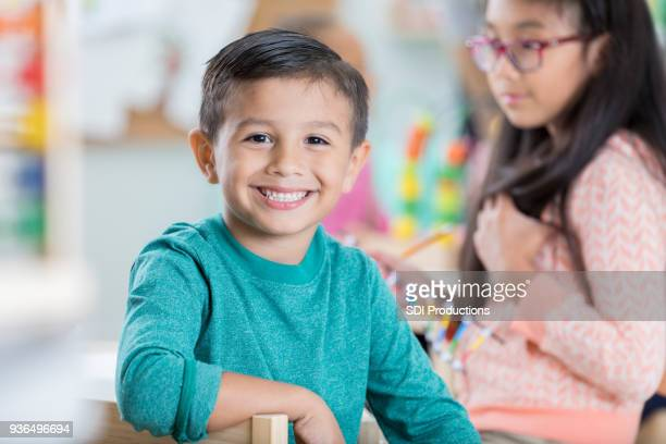 adorable kindergarten schoolboy in the classroom - primary age child stock pictures, royalty-free photos & images
