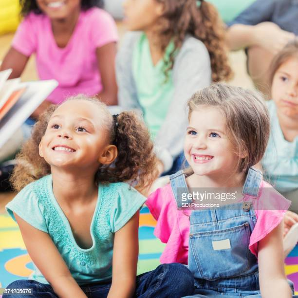 adorable kindergarten students listen during story time - storyteller stock pictures, royalty-free photos & images