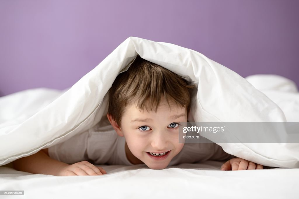 Adorable laughing boy playing in bed under a white blanket : Stock Photo
