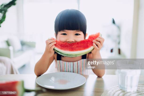 adorable little asian girl eating a slice of watermelon at home - indulgence stock pictures, royalty-free photos & images