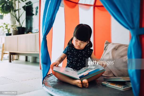 adorable little asian girl enjoying herself and spending leisure time at home. she is reading book with her teddy bear in a tent at home - reading stock pictures, royalty-free photos & images