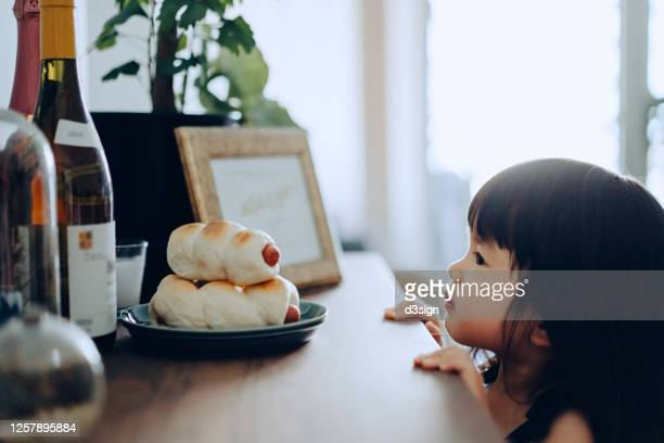 adorable little asian girl peeking over cabinet and sneaking freshly baked homemade bread at home - temptation stock pictures, royalty-free photos & images