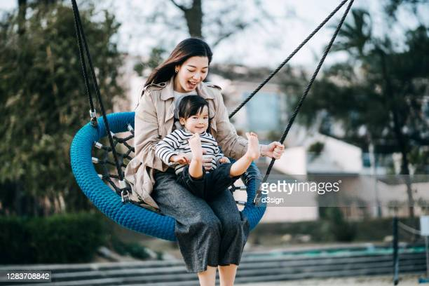 adorable little asian girl sitting on her mother's lap, having fun and playing on a basket swing in a park. smiling joyfully and enjoying quality mother and daughter family bonding time together - moving activity stock pictures, royalty-free photos & images