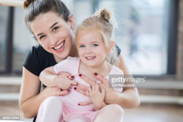 adorable little ballerina smiles for camera with dance instructor - little girls dressed up wearing pantyhose stock photos and pictures