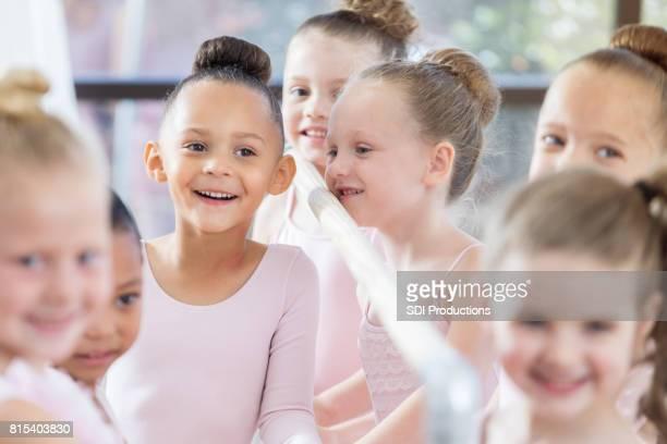 Adorable little ballerina smiles joyfully during class