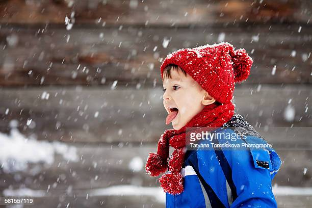 Adorable little boy, catching snowflakes outdoor