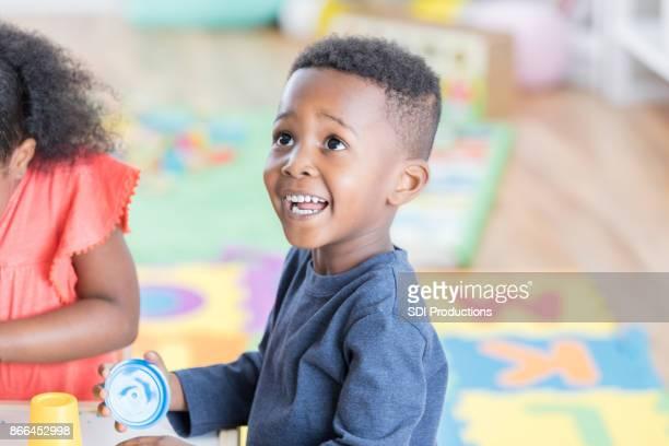 Adorable little boy enjoys playing in preschool classroom
