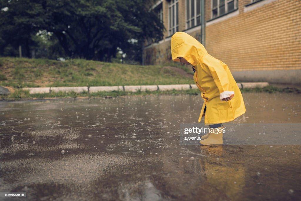 Adorabile ragazzino che gioca al giorno delle piogge : Foto stock
