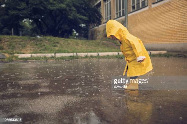 adorable little boy playing at rainy day - puddle stock pictures, royalty-free photos & images