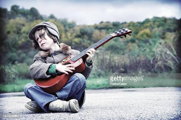 Adorable petit garçon jouant de la guitare sur Prairie