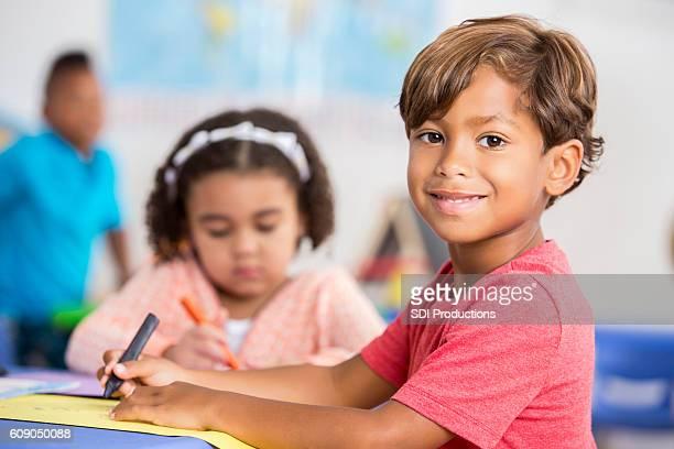 Adorable little boy smiles in his preschool class