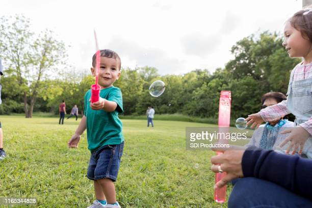 adorable little boy smiles while playing with bubble wand - niece stock photos and pictures