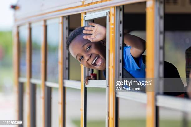 adorable little boy waves from school bus - field trip stock pictures, royalty-free photos & images