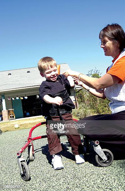 adorable little boy with a disability learning to use a walker to make his way around the playground at school. - cerebrum stock pictures, royalty-free photos & images