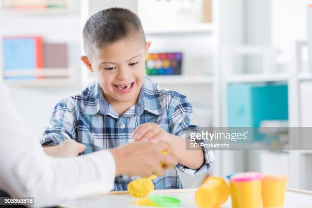 Adorable little boy with Down syndrome enjoys playdough