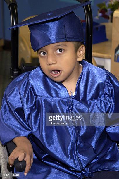 adorable little boy with multiple disabilities impatiently awaiting the start of his preschool graduation ceremony. - cerebrum stock photos and pictures