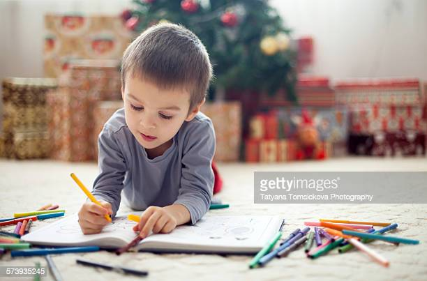 Adorable little boy, writing in a book, lying