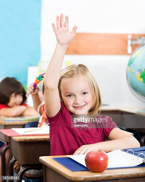 adorable little caucasian girl raising hand in elementary classroom - short sleeved stock photos and pictures