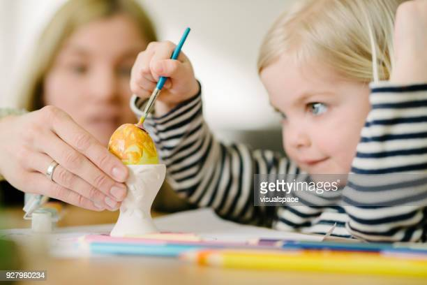 adorable little cute girl paints colourful easter egg - happy easter mom stock pictures, royalty-free photos & images