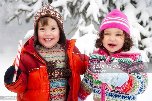 Adorable Little Girl and Boy Playing in the Snow Together