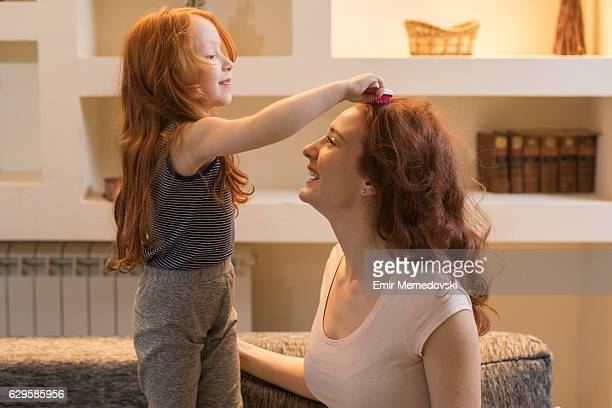 Adorable little girl combing her mother's  hair.