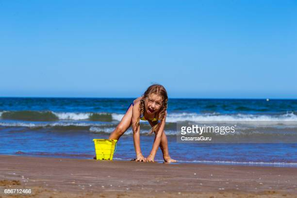 adorable little girl enjoy the sandy valencia beach - little girls bent over stock photos and pictures