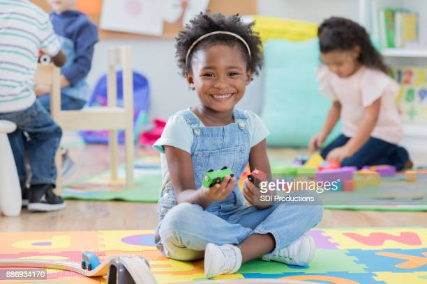 adorable little girl enjoys time at day care - sitting on ground stock pictures, royalty-free photos & images