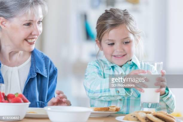 Adorable petite fille a petit déjeuner avec sa grand-mère