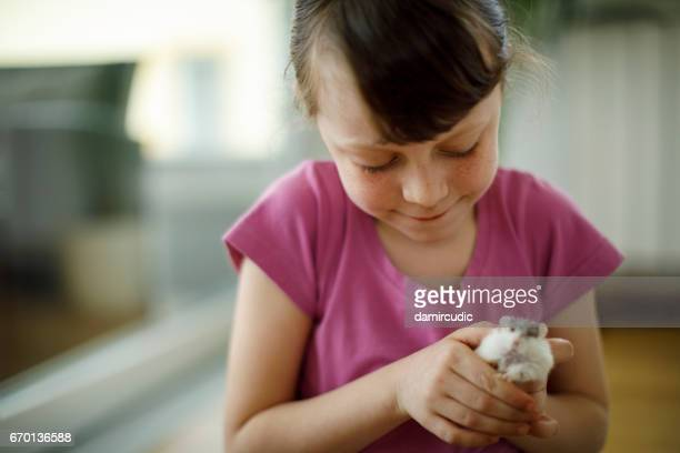 Adorable petite fille tenant son hamster