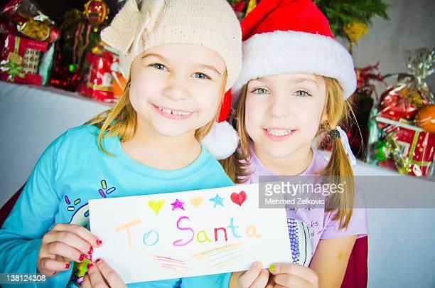Adorable little girl holding letter to Santa