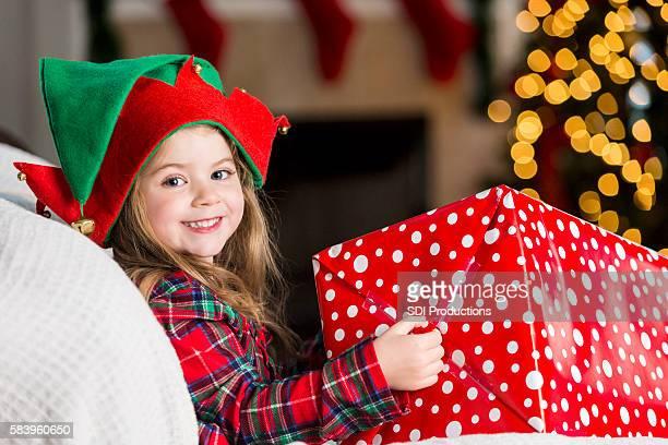 Adorable little girl holds big Christmas gift on Christmas morning