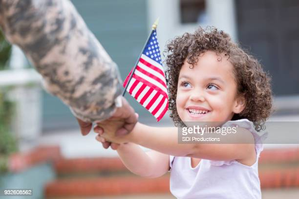 adorable little girl holds her military dad's hand - military flags stock photos and pictures