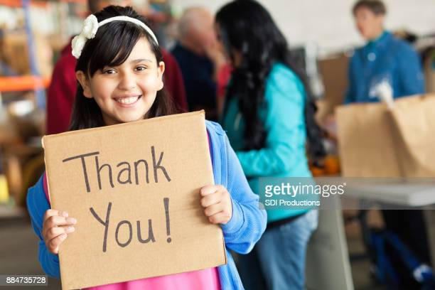 adorable little girl holds thank you sign during food drive - charity and relief work stock pictures, royalty-free photos & images