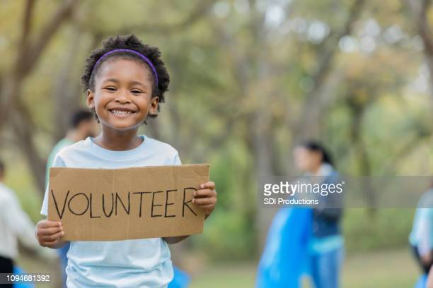 """adorable little girl holds up """"volunteer"""" cardboard sign outdoors - altruism stock pictures, royalty-free photos & images"""