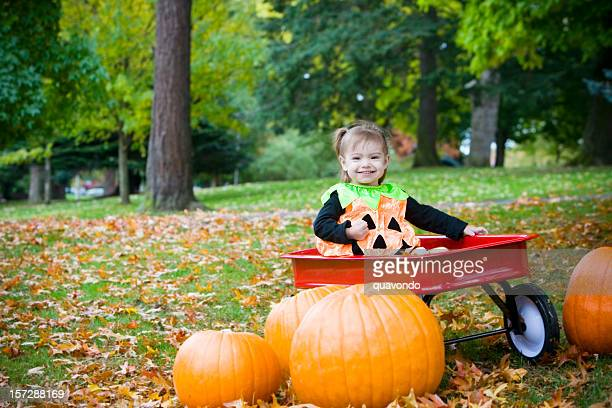 adorable little girl in halloween pumpkin costume on fall day - toy wagon stock photos and pictures