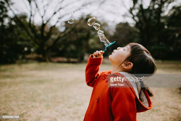 Adorable little girl in red coat blowing bubbles in park