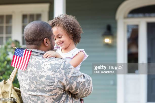 adorable little girl is excited to see army dad - patriotic stock pictures, royalty-free photos & images