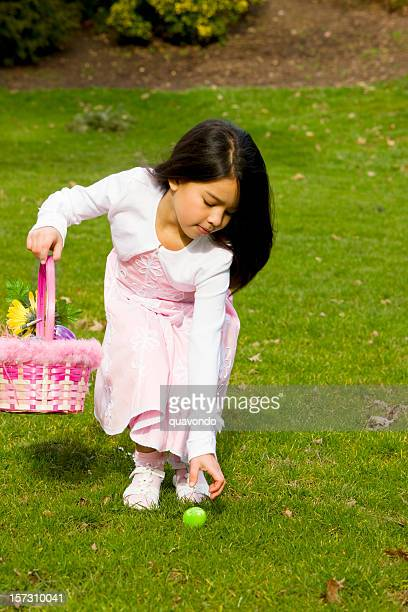 adorable little girl on easter egg hunt outdoors, copy space - little girls bent over stock photos and pictures