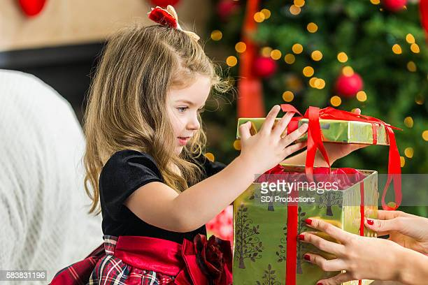 Adorable little girl opening her Christmas present