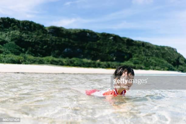 adorable little girl playing on beach with shallow water, japan - 鹿児島県 ストックフォトと画像