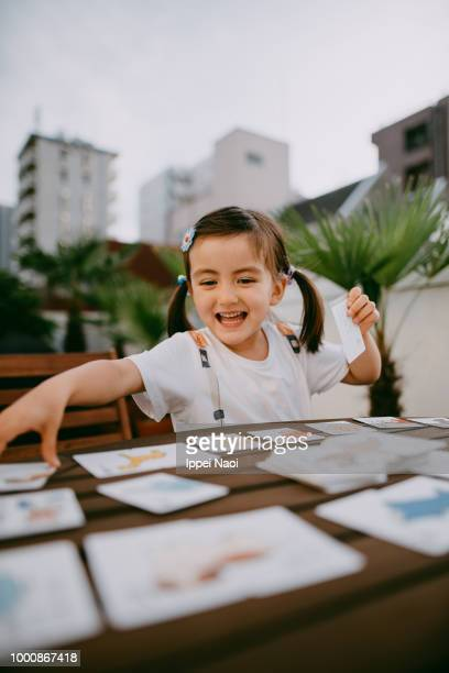 Adorable little girl playing with cards