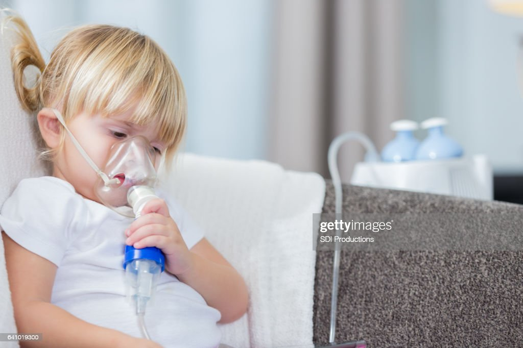 Adorable little girl receives breathing treatment : Stock Photo