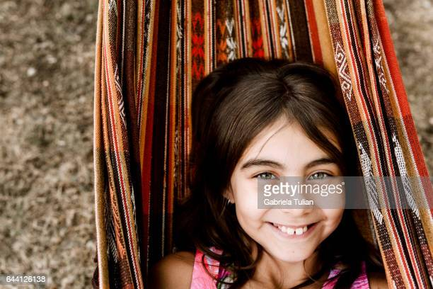 Adorable little girl resting in a hammock on the beach