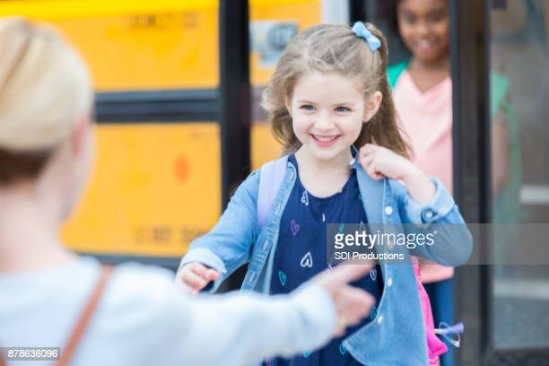 Adorable little girl runs to mom after school