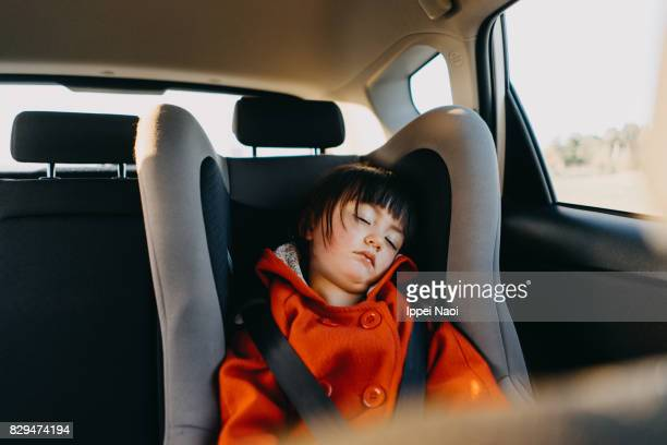 adorable little girl sleeping in car - kids inside car stock photos and pictures
