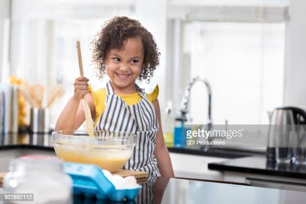 Adorable little girl smiles as she mixes batter for baking